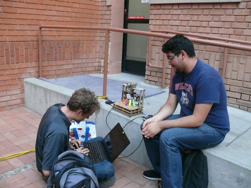 Two students outside working on maker project