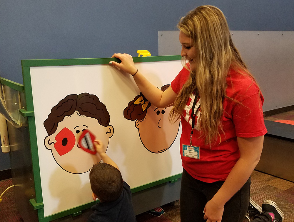 Linguistics student helping K-12 student at interactive event