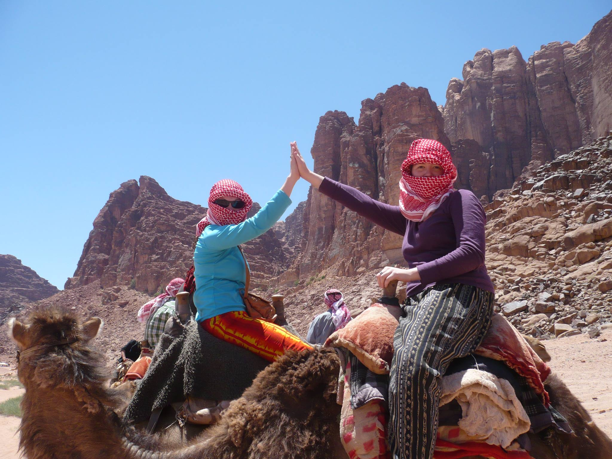 Two female students riding camels and high fiving