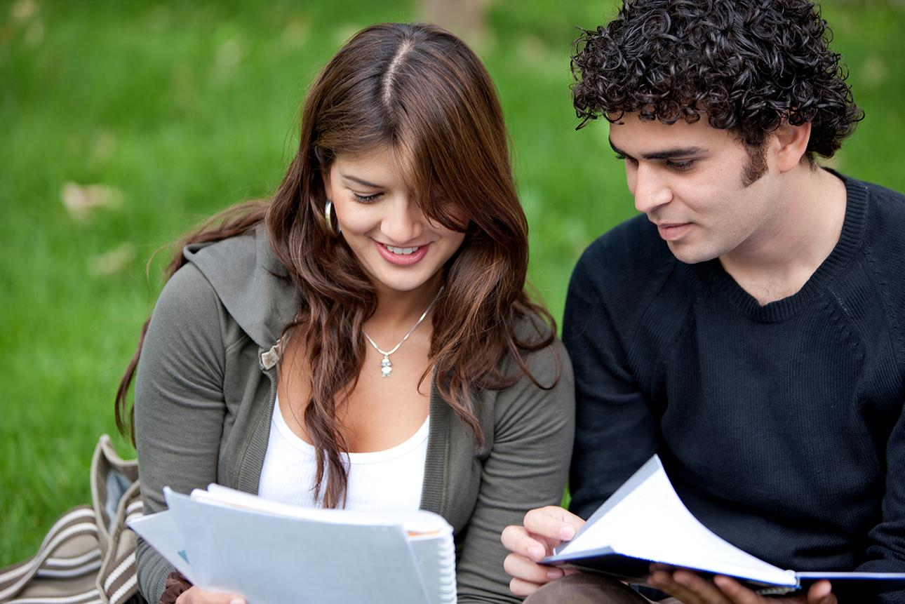 Two students looking at papers while sitting in the grass