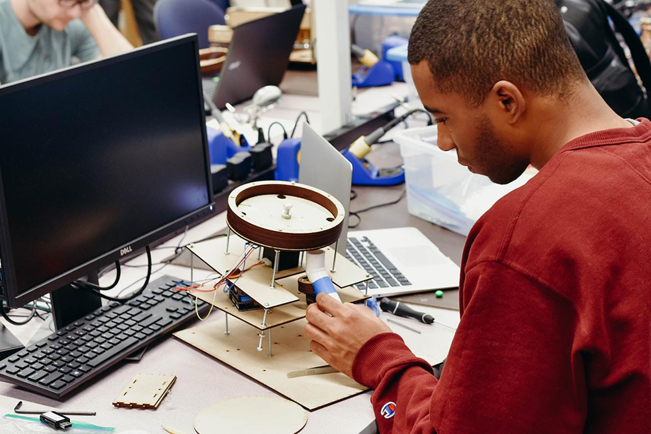 Male student building a skittle sorting machine in computer lab