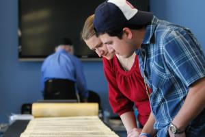 Two students looking at ancient scroll