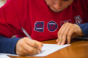 Male student wearing red UA shirt writing at desk
